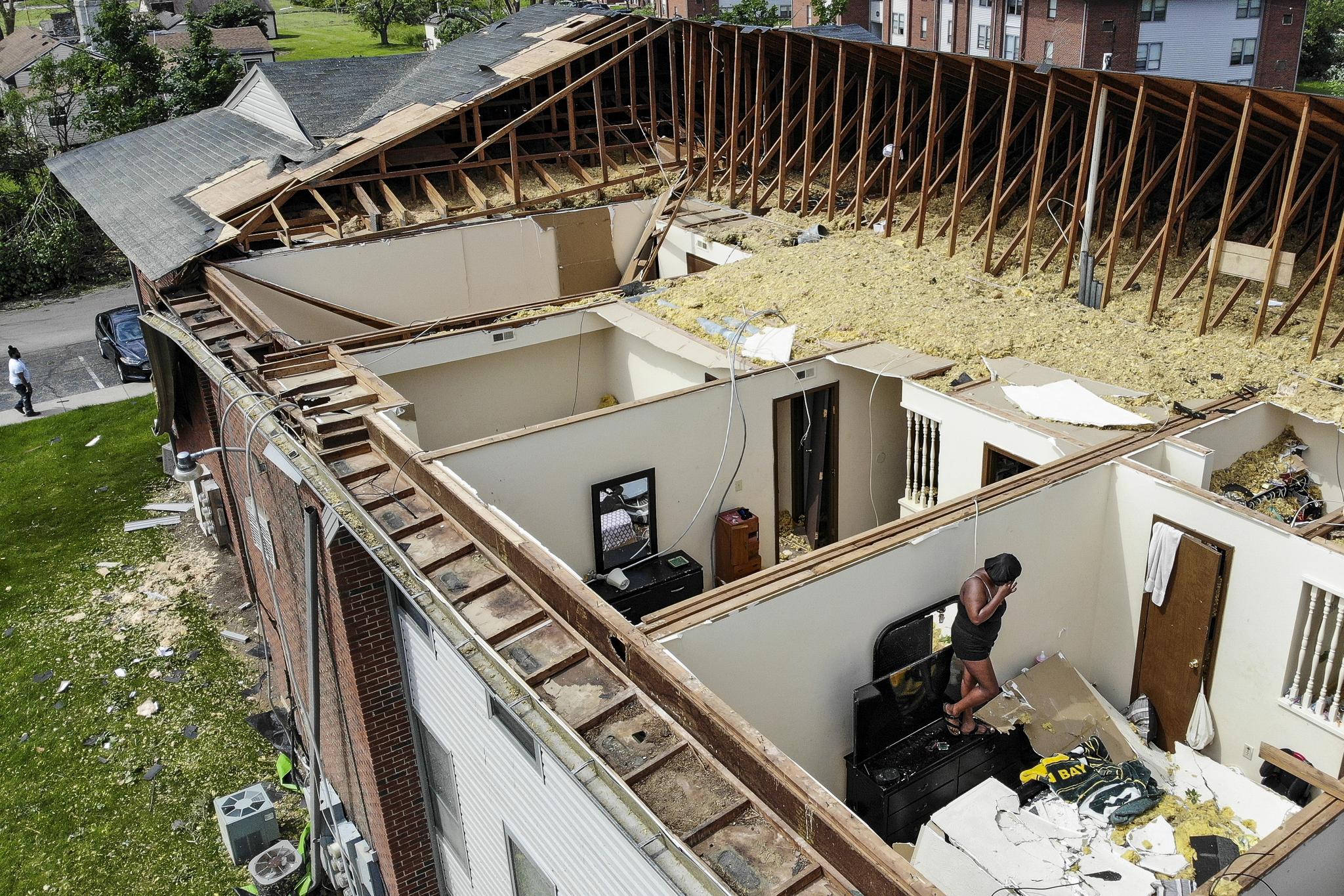 28일(현지시간) 미 오하이오주 트로트우드 지역의 아파트가 토네이도로 지붕이 날아간 뒤 한 주민이 집 내부를 살피고 있다. [AP=연합뉴스]