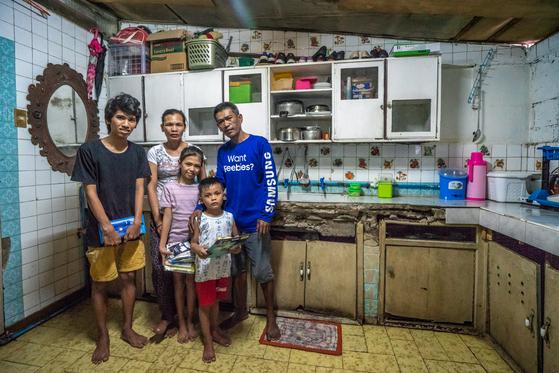 컴패션 비전트립팀이 지난해 방문한 에리카(사진 왼쪽에서 세 번째)와 매키(네 번째) 가족의 새집. 다섯 식구가 부엌 한편에 서서 포즈를 취하고 있다. 컴패션은 리키가 양육 프로그램을 수료하고 자립할 때까지 이 집에서 살 수 있도록 했다. [사진 한국컴패션]