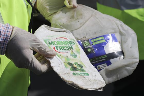 말레이시아 관리가 28일(현지시간) 클랑항에서 호주에서 온 플라스틱 쓰레기를 들어보이고 있다. [AP=연합뉴스]
