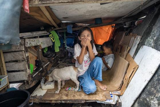 개그우먼 이성미 씨가 필리핀 마닐라에서 만난 에리카(사진 앞쪽)와 남동생 매키. 나무판을 얹은 좁은 수레가 남매와 개의 보금자리다. 개그우먼 이성미 씨는 비전트립에서 사진 속 이 아이들을 만났다. [사진 한국컴패션]