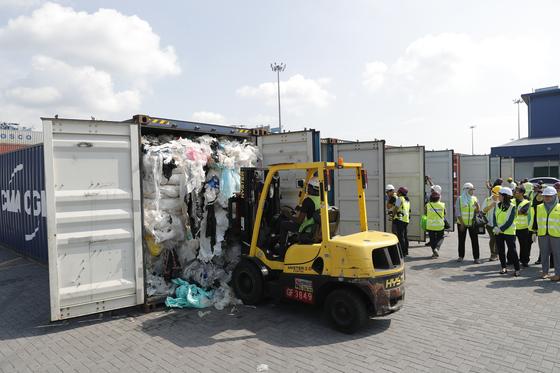 말레이시아 환경부 관리들이 28일(현지시간) 클랑항에서 플라스틱 쓰레기 컨테이너를 조사하고 있다. [AP=연합뉴스]
