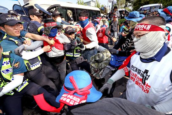 22일 서울 현대사옥 앞 민주노총 금속노조 집회에서 조합원들이 경찰의 보호장구와 방패를 빼앗고 폭행했다. 경찰 30여 명이 다쳤고 일부는 치아가 부러지거나 인대가 늘어났다. [뉴스1]