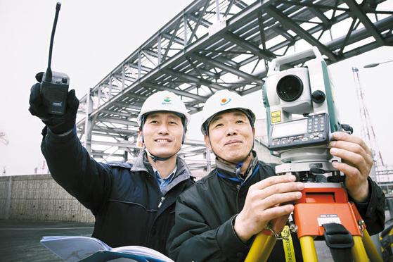 전남 여수시 국가산업단지에 있는 GS칼텍스 공장에서 직원이 협력 업체인 우주종합건설 직원과 생산설비 건설을 위한 측량 작업을 하고 있다.  [사진 GS칼텍스]
