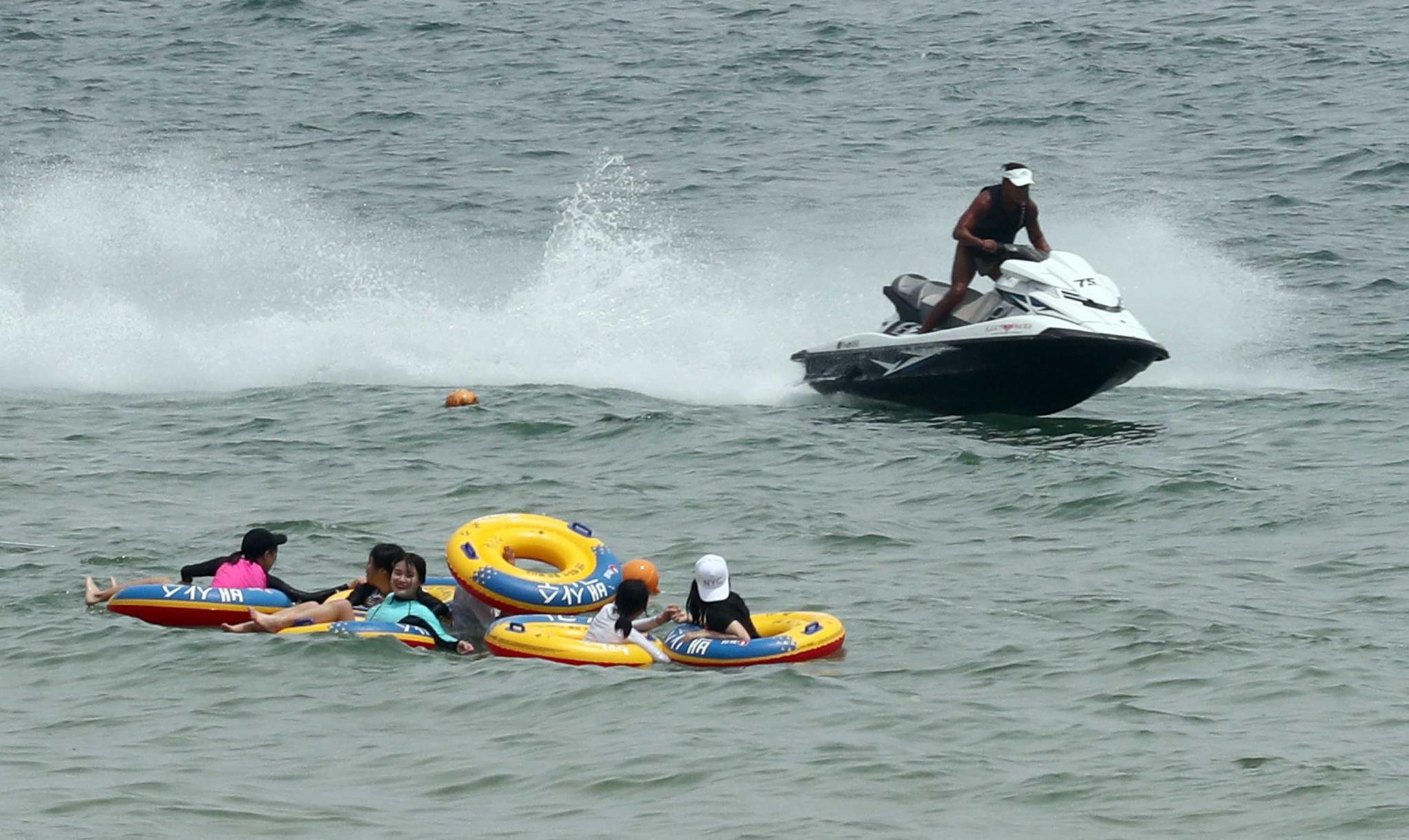 1일 부산 해운대해수욕장에서 물놀이를 즐기는 피서객 옆으로 수상 오토바이가 물보라를 일으키며 질주하고 있다. [연합뉴스]