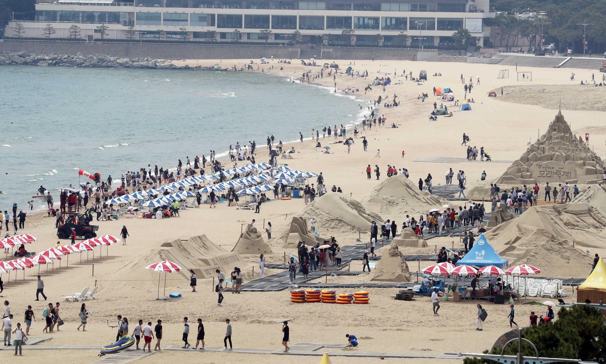 1일 부산 해운대해수욕장을 찾은 피서객들이 해변에서 더위를 식히고 있다. 오른쪽은 해운대 모래축제 풍경. 부산지역 3개 해수욕장은 8월 31일까지 운영된다. [연합뉴스]