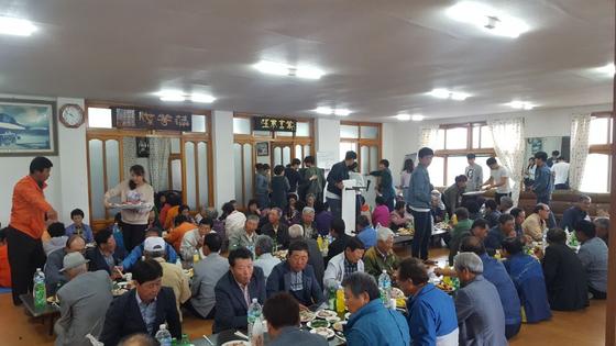 마을 어르신들과 함께 식사를 하고 있는 모습. [사진 글로벌제주문화협동조합]