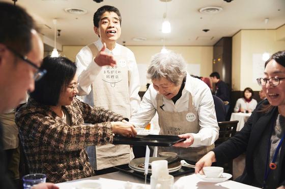 일본의 '주문을 잘못 알아듣는 식당'에서 치매 노인들이 손님들에게 서빙을 하고 있다. 치매 노인들이 주문과 다른 엉뚱한 음식을 가져와도 불평하는 손님은 한명도 없다. [사진 '주문을 잘못 알아듣는 식당' 실행위원회 페이스북]