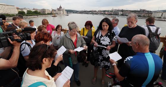 헝가리 부다페스트 다뉴브강 유람선 침몰사고 엿새째인 3일 오후(현지시간) 다뉴브강 머르기트 다리에 모인 헝가리 시민들이 '허블레아니호' 사고 희생자에 대한 추모와 실종자의 무사귀환을 기원하며 '아리랑'을 부르고 있다. [뉴스1]