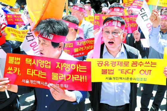 서울개인택시운송사업조합 관계자들이 지난달 21일 서울 여의도 더불어민주당 당사 앞에서 집회를 갖고 승합차 공유 서비스 '타다'의 퇴출을 요구하고 있다.