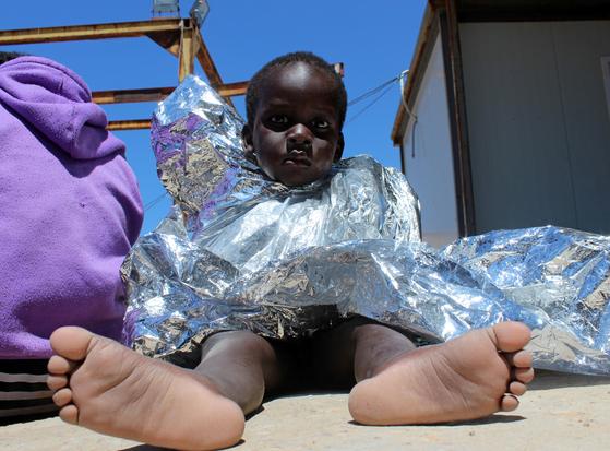 지난 2일 지중해를 건너 이탈리아로 향하다 리비아 서부 트리폴리 인근 해상에서 침몰한 선박에서 구조된 이주민 어린이가 저체온증 방지를 위해 알루미늄 호일로 감싼 담요를 덮고 있다. [로이터=연합뉴스]