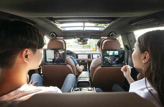 SK텔레콤 홍보모델들이 차량 내 스크린을 통해 풀HD 화질의 실시간 방송과 개인 맞춤형 TV광고를 감상하고 있는 모습. [사진 SK텔레콤]