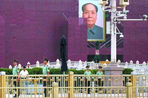 천안문 사태 30주년을 맞은 4일 중국 베이징 천안문에 걸린 마오쩌둥 전 국가주석의 초상화 앞에서 공안들이 보초를 서고 있다. 천안문 사태는 1989년 6월 4일 민주화를 요구하는 학생과 시민을 중국 정부가 무력으로 진압한 사건이다. [AP=연합뉴스]