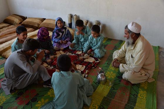 지뢰 폭발로 다리를 잃은 아프가니스탄 어린이들이 책상도 없는 학교에서 공부를 하고 있다. [AFP=연합뉴스]