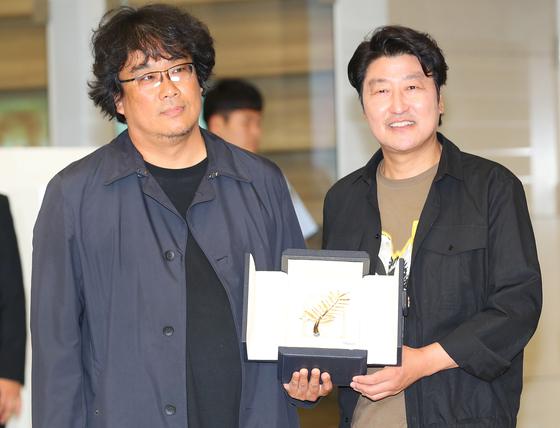 공항 귀국장에서 황금종려상을 들고 있는 봉준호 감독과 배우 송강호씨. [중앙포토]