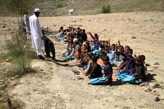 지난 달 29일 (현지시간) 아프가니스탄 난가르 주 하스킨에서 학생들이 맨땅에서 수업을 받고 있다. [신화=연합뉴스]
