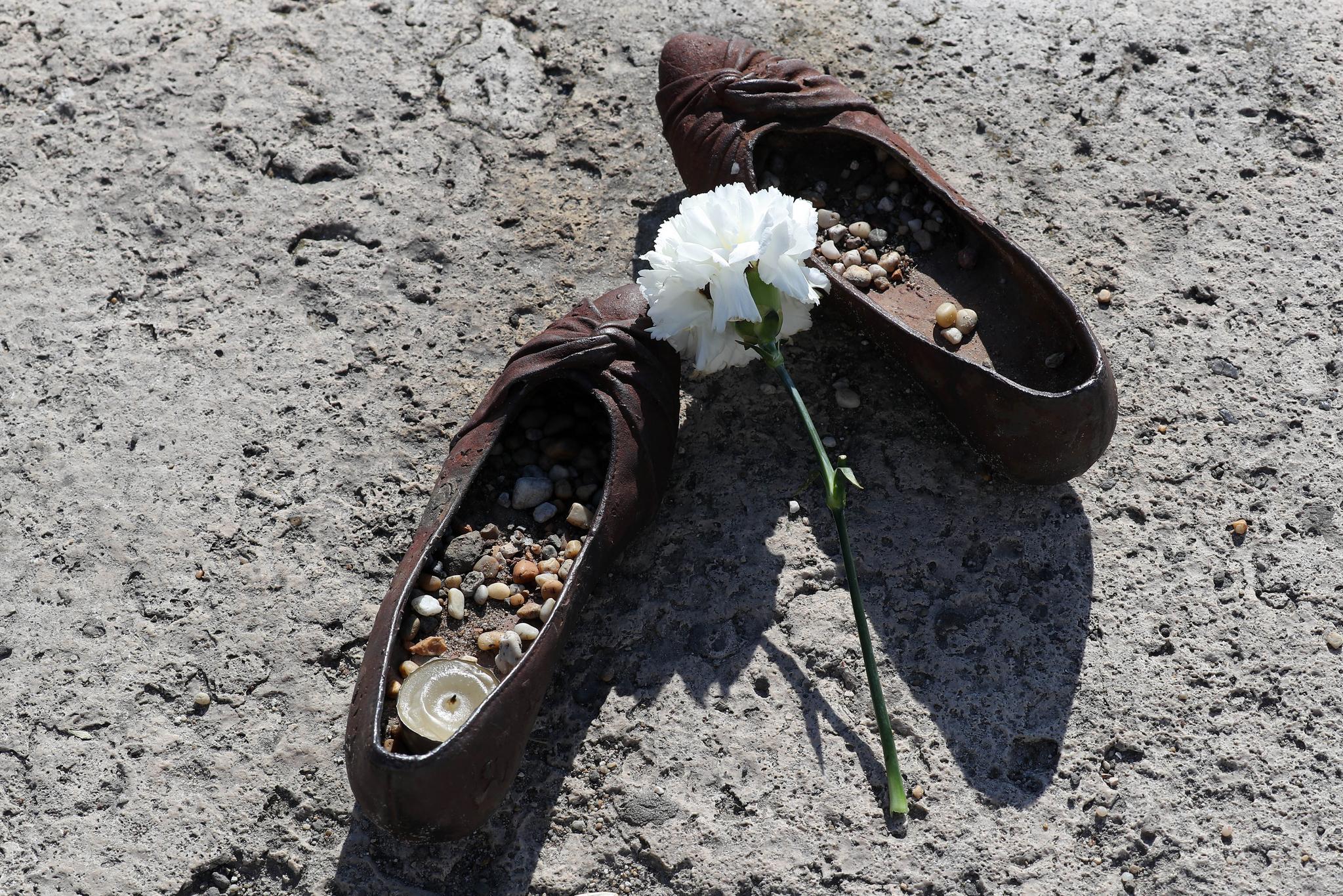 4일(현지시간) 헝가리 부다페스트 다뉴브강 머르기르트 다리와 세체니 다리 사이에 설치된 '다뉴브 강가의 신발들'에 누군가가 준비한 꽃이 놓여져 있다. 이곳은 2차 세계대전 당시 나치가 유대인들에게 신발을 벗게 한 뒤 총살한 곳으로, 2005년 이들을 추모하기 위한 60켤레의 신발 조형물 '다뉴브 강가의 신발들'이 세워졌다. [연합뉴스]