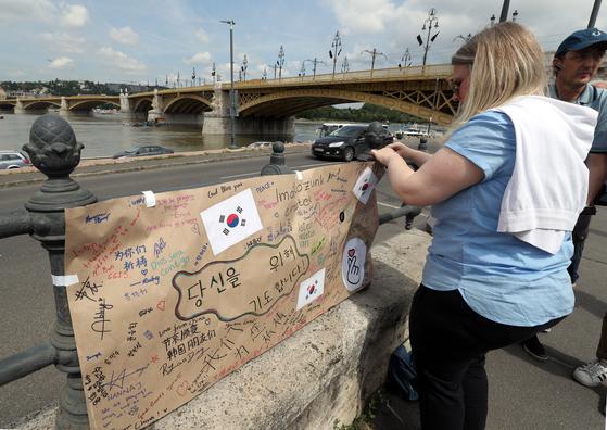 5일 오전 (현지시간) 헝가리 부다페스트 다뉴브강변에서 헝가리 국제학교 학생들이 유람선 '허블레아니호' 희생자를 애도하는 추모 메시지를 붙이고 있다. [뉴스1]