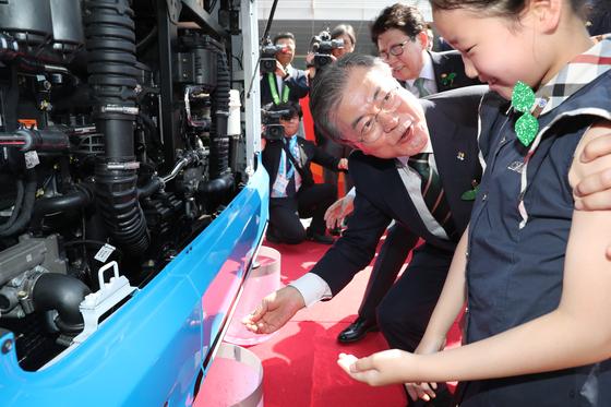 문재인 대통령이 5일 창원컨벤션센터에서 열린 ' 환경의 날' 행사에 참석했다. 문 대통령이 어린이와 함께 수소버스를 시승하기에 앞서 배출되는 물을 만져보고 있다. [연합뉴스]