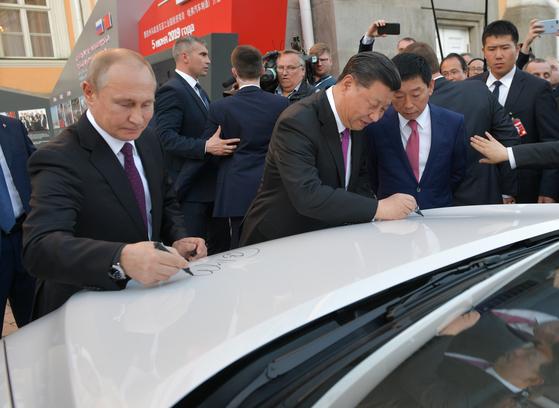 러시아를 국빈 방문 중인 시진핑 중국 국가주석(오른쪽)이 5일(현지시간) 모스크바 크렘린 궁에서 블라디미르 푸틴 러시아 대통령과 함께 러시아산 중국 차 하발 F7 SUV 차량에 사인하고 있다. 양국 정상은 이날 단독·확대 정상회담을 갖고 통상·경제 협력방안을 논의했다. [EPA=연합뉴스]