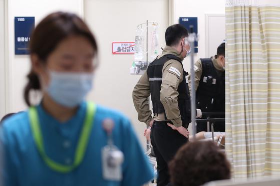 한 병원 응급실에서 환자가 의료진의 통제에 따르지 않고 폭력적인 언행을 계속하자 보안 직원들이 대응하고 있다. <저작권자(c) 연합뉴스, 무단 전재-재배포 금지>