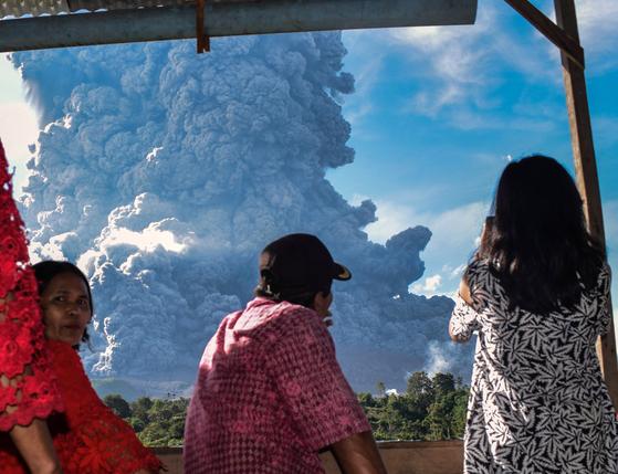 수마트라섬 주민들이 9일 오후 시나붕 화산에서 내뿜는 연기를 걱정스런 표정으로 바라보고 있다.[연합뉴스]