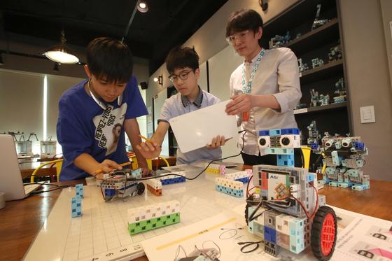 판교 최대 코딩학원 '디랩 판교캠퍼스' 의 메이커 스페이스에서 강사와 학생들이 길찾기 로봇을 시연해 보고 있다. 오종택 기자