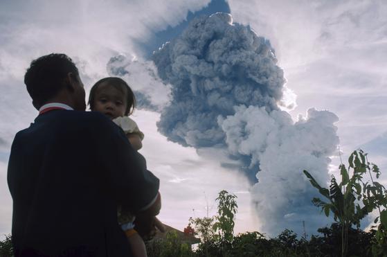 아이를 안은 아버지가 9일 수마트라섬에서 시나붕 화산 폭발을 쳐다보고 있다.[AP=연합뉴스]