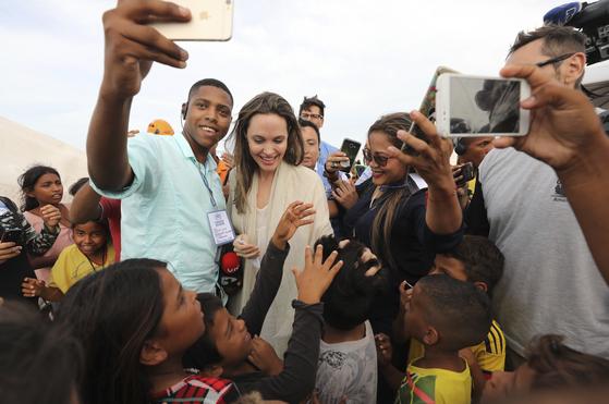 영화배우 안젤리나 졸리가 8일 콜롬비아 마이카오에 있는 난민촌을 찾았다. 베네수엘라 난민들은 물론 유엔난민기구 현지직원들까지 몰려 들어 기념사진을 찍고 있다.[AP=연합뉴스]