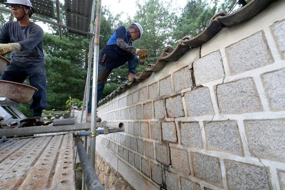 2016년 9월 12일 경북 경주에서 발생한 지진으로 경주 통일전 본전 회랑 외벽 기와에 균열이 발생해 보수 업체 직원이 기와를 보수하는 모습. [중앙포토]