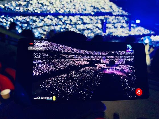 BTS는 V라이브를 통해 웸블리 공연 전체를 라이브 스트리밍 서비스를 했다. 인당 3만3000원 뿐 아니라 디지털 응원봉 판매 등 모바일로 상당한 수익을 올렸다. [사진 V라이브 캡처]