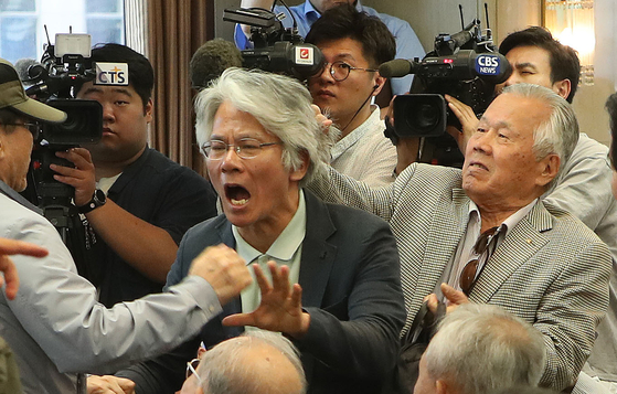 전광훈 목사가 11일 서울 세종로 프레스센터에서 기자회견을 열고 '문재인 대통령 하야'를 촉구했다. 한 참석자가 항의하다 머리끄덩이를 잡혀 쫓겨나고 있다. 오종택 기자