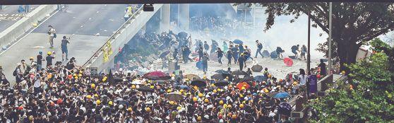 홍콩 정부의 '범죄인 인도 법안' 추진에 반대하는 시민들이 12일(현지시간) 정부청사 인근 애드머럴티 지역에서 최루탄을 쏘는 경찰들을 피해 도망치고 있다. 홍콩 정부는 이날 시위가 격화할 양상을 보이자 법안 심의를 연기했다. [로이터=연합뉴스]