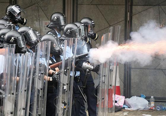 홍콩 경찰들이 12일(현지시간) 시위대를 향해 최루탄을 발사하고 있다. [로이터=연합뉴스]