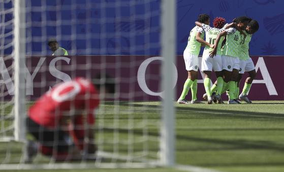 나이지리아 선수들이 12일 열린 여자월드컵 A조 조별리그 2차전에서 두 번째 골이 터진 뒤 기뻐하고 있다. 골문에서 망연자실하는 한국 선수와 대조를 이루고 있다. [AP=연합뉴스]