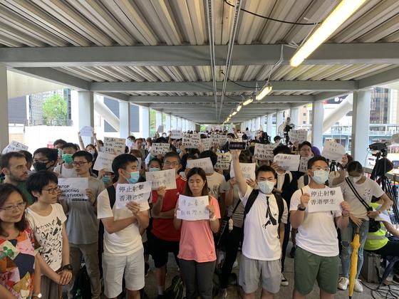 13일 오후 홍콩 입법원과 이어지는 육교에서 시민들이 전날 경찰의 최루탄, 고무탄 발사 등 과잉 폭력 진압에 반대하는 피켓을 들고 시위하고 있다. 신경진 기자
