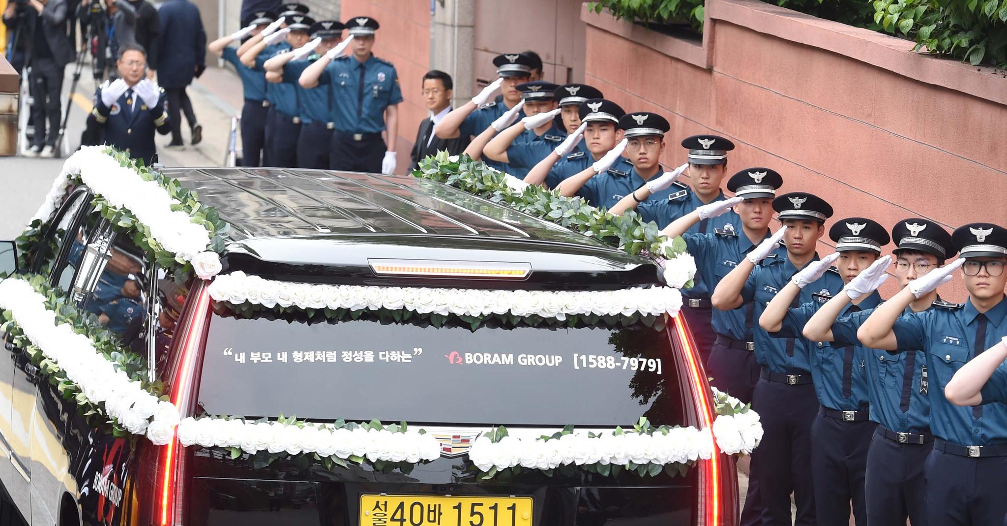 14일 오전 서울 마포구 사저 앞에서 경찰들이 김대중 전 대통령의 부인 고 이희호 여사의 운구차를 향해 거수경례를 하고 있다. 우상조 기자