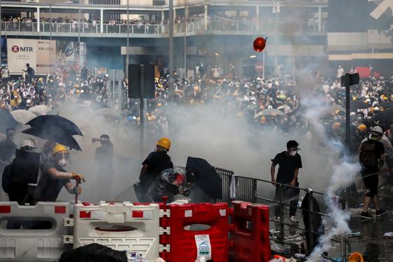 지난 6월 9일 범죄인 인도 법안을 거부하며 시작된 홍콩 시위는 멈출 줄 모르고 계속되고 있다. 12일 홍콩 거리에서 경찰이 최루탄을 발사하자 시민들과 취재진이 흩어지고 있다. [로이터=연합뉴스]