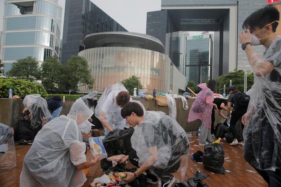 홍콩 입법기관인 입법회 바깥에서 비옷을 입은 학생들이 쓰레기를 치우고 있다. 홍콩 시위는 시민 정신을 보여주는 비폭력 시위로 진행 중이다. 시민들은 관공서와 거리를 보호하며 사위를 벌이고 있다. [로이터=연합뉴스]