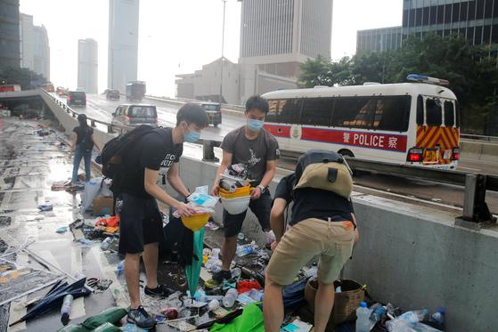 13일 홍콩 거리에서 학생들이 시위 현장에 쌓인 쓰레기를 치우는 뒤로 홍콩 경찰 버스가 지나고 있다. 홍콩 주민들은 이번 시위를 계기로 민주주의와 인권을 앞세우는 홍콩인의 정체성을 더욱 강화할 것으로 예상된다. [로이터=연합뉴스]