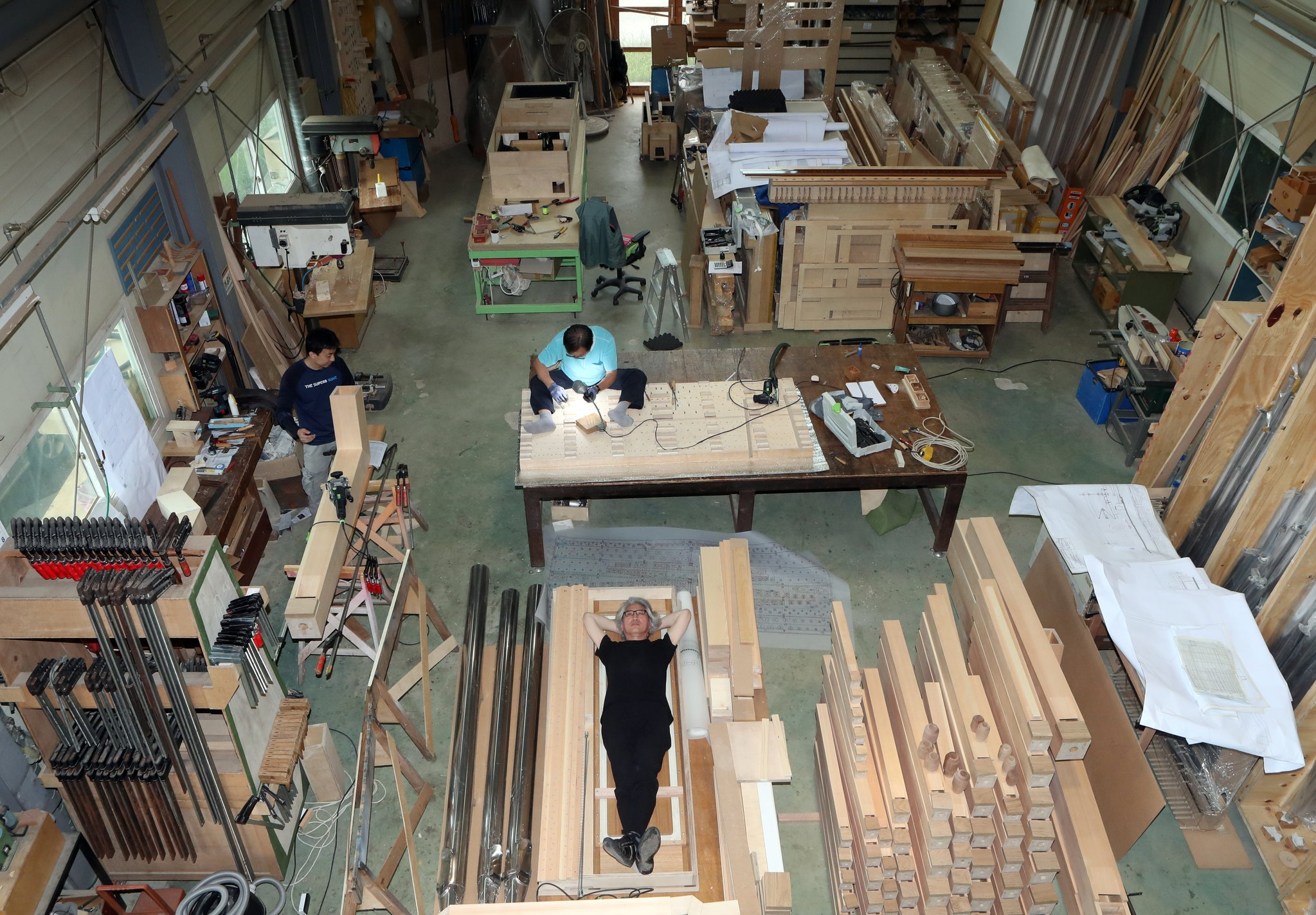 홍성훈씨가 경기도 양평 자신의 작업실에 누웠다. 금속 파이프와 목재, 도구들로 빼곡하다. 최정동 기자