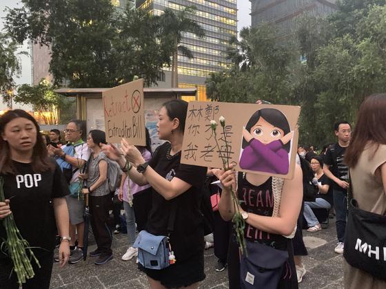 14일 오후 홍콩섬 차터 가든에서 열린 홍콩 어머니 집회에 참석한 시민이 송환법 처리 반대 피켓을 들고 있다. [홍콩=신경진 기자]