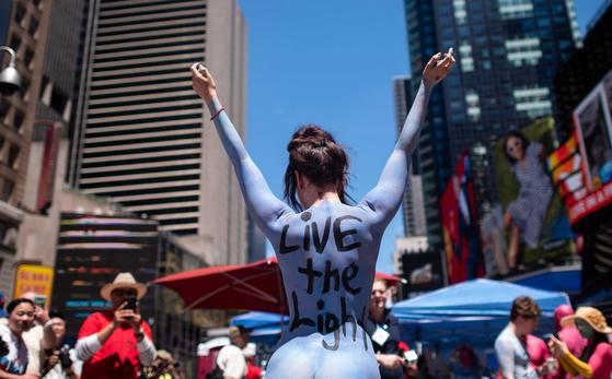 15일(현지시간) 미국 뉴욕 타임스퀘어 거리에서 바디페이팅을 한 알몸 시위대가 거리에 나섰다. 이날 한 시위자가 포즈를 취하고 있다. [AP=연합뉴스]