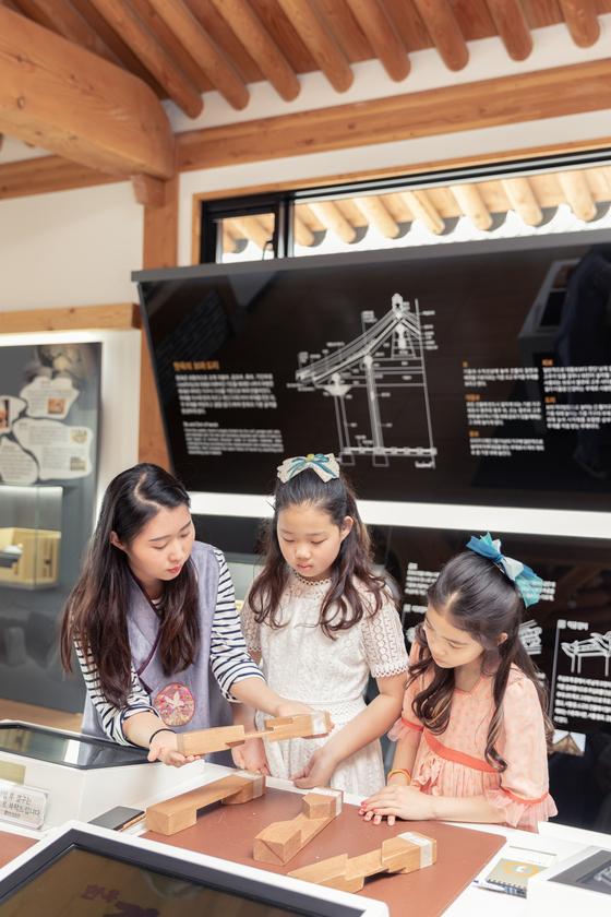 김민수(왼쪽) 도슨트의 지도에 따라 허시은(가운데)·이수안 학생모델이 '블럭 맞추기' 같은 한옥 자재 조립을 공부하고 있다.