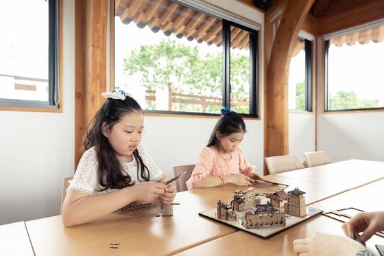 허시은(왼쪽)·이수안 학생모델이 수원한옥기술전시관 2층에서 수원화성 만들기 체험에 나섰다.