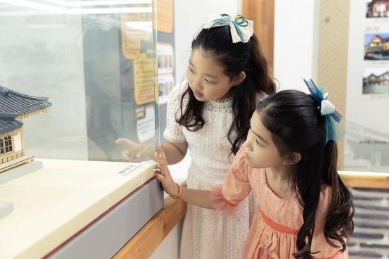 (왼쪽)허시은·이수안 학생모델이 수원한옥기술전시관 신한옥 소개 구역에서 전시물을 자세히 살피고 있다.