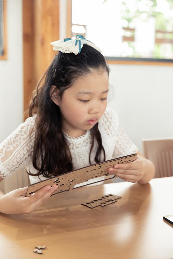 허시은 학생모델이 수원한옥기술전시관에서 수원화성 만들기 체험을 하고 있다.