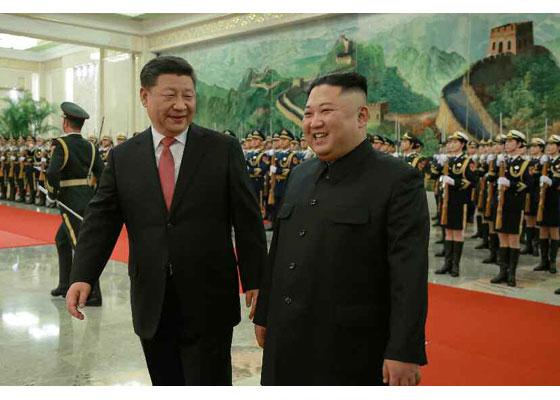 북한 노동당 기관지 노동신문이 김정은 국무위원장의 4차 방중 소식을 올올 1월 10일자 지면에 보도했다. 사진은 김 위원장이 시진핑(習近平) 중국 국가 주석과 1월 8일 중국 인민대회당에서 인민해방군의 사열을 받는 모습. [뉴스1]