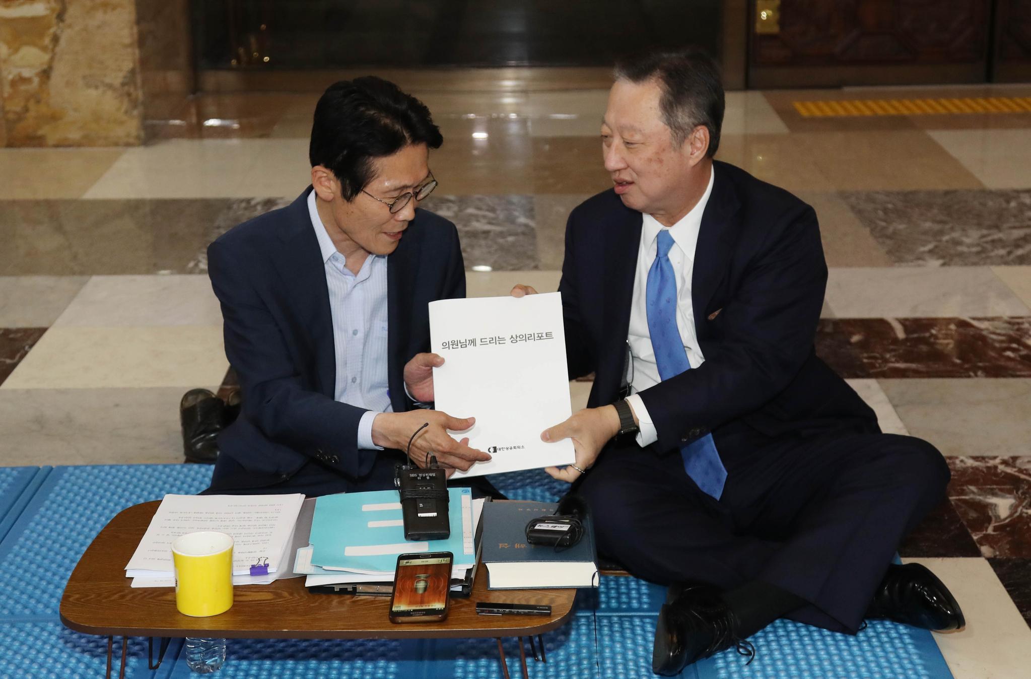 박용만(오른쪽) 대한상공회의소 회장이 17일 국회를 찾아 정의당 윤소하 원내대표에게 '경제활성화를 위한 조속입법 과제' 리포트를 전달하고 있다. [사진 대한상공회의소]