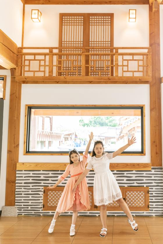 이수안(왼쪽)·허시은 학생모델이 수원한옥기술전시관 1층 전면 유리창 앞에서 '마음의 눈'을 여는 퍼포먼스를 펼쳐 보였다. 한옥기술전시관의 커다란 창문들은 신한옥의 개방성, 소통성을 상징한다.