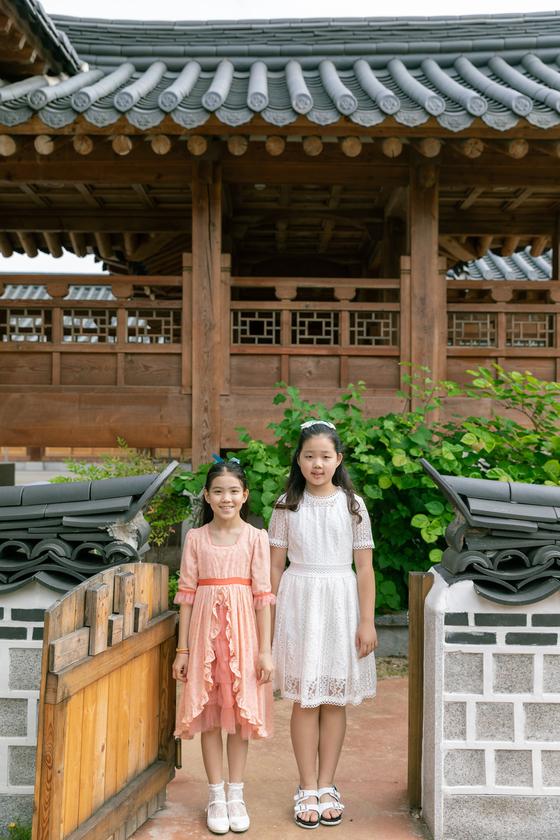 이수안(왼쪽)·허시은 학생모델이 각자 신한옥에 어울릴 법한 드레스를 입고 수원 장안사랑채 뒤뜰에 서 있다. 장안사랑채는 국토교통부 '2018 대한민국 한옥공모전'에서 한옥대상을 받았다.